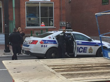 Police lead a person working at the marijuana dispensary out in handcuffs, taken away in police car.