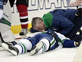 A trainer talks to Vancouver Canucks defenceman Philip Larsen, of Finland, after he was knocked down on a hit by New Jersey Devils left wing Taylor Hall during the second period of an NHL hockey game, Tuesday, Dec. 6, 2016, in Newark, N.J. Larsen left the game on a stretcher.
