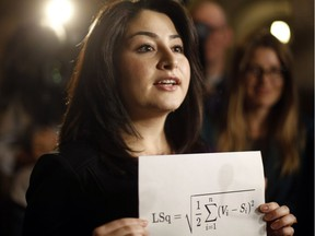 To criticize the electoral reform report, Minister for Democratic Institutions Maryam Monsef holds up a piece of paper with a complicated mathematical equation on December 1, 2016.
