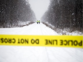 Members of Ottawa Police's Emergency Services Unit walk down the train line that crosses McCarthy Road looking for evidence from the double-homicide of sisters Nasiba and Asma A-Noor.