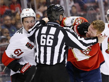 Ottawa Senators right wing Mark Stone (61) and Florida Panthers defenseman Michael Matheson fight as linesman Darren Gibbs separates them during the first period of an NHL hockey game, Tuesday, Jan. 31, 2017, in Sunrise, Fla.