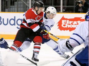 Ottawa's Artur Tyanulin wrestles for the puck with Mississauga's Jacob Moverare  in front of Mississauga's net during first-period action between the Ottawa 67s (red) and the Mississauga Steelheads at TD Place Tuesday (Jan. 24, 2017) evening.