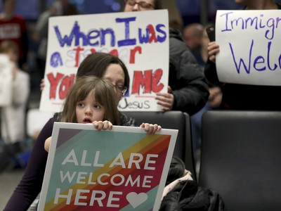 Rachel Walker, centre, of St. Paul and her daughter, Evelyn, 7, front, join others in protesting an executive order signed by U.S. President Donald Trump restricting immigration from several Muslim nations Saturday, Jan. 28, 2017, at the Minneapolis-St. Paul International Airport.