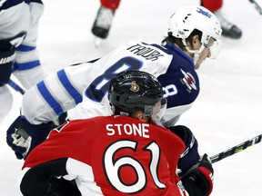 The Ottawa Senators' Mark Stone is hit by the Winnipeg Jets' Jacob Trouba (8) during the third period on Sunday, Feb. 19, 2017. The NHL has suspended Trouba for two games for an illegal check to the head.