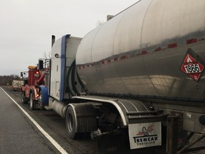 A tow truck hooks up a tanker trailer that lost a wheel Friday morning, striking five other vehicles.