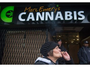 A woman smokes a joint as police officers stand outside the Cannabis Culture shop during a police raid, in Vancouver, B.C., on Thursday March 9, 2017. Jodie Emery, who says the Liberals' new pot legislation is prohibition 2.0, is one of the co-founders of the chain of dispensaries.
