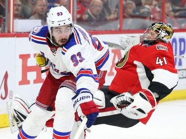 Craig Anderson of the Ottawa Senators is tripped up by Mika Zibanejad of the New York Rangers.