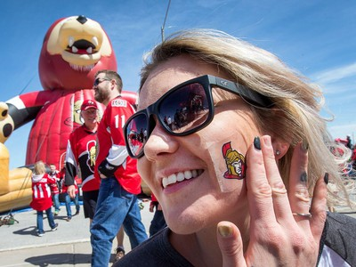 Lezlie Cooper, who came to Ottawa for games 1 and 2 from Goose Bay, Labrador, sticks a Sens sticker on her cheek while enjoying the action in the Red Zone.