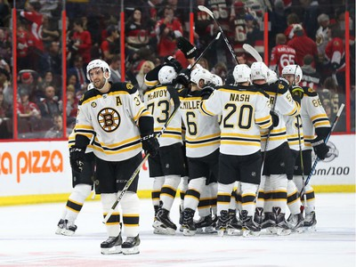 Patrice Bergeron, left, and the Boston Bruins celebrate their double-overtime win.