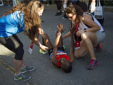 A woman gets help after falling to the ground after crossing the 10K finish line.