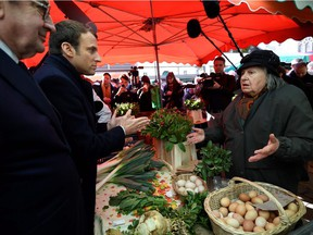 Emmanuel Macron, now the French president, speaks with a vendor on April 29, 2017 on a market in Poitiers, central France, while campaigning. The markets, writes Andrew Cohen, are but one symbol of France's beauty and culture.