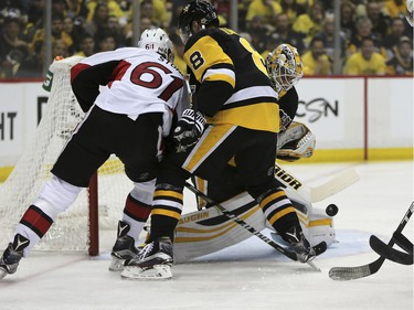 Pittsburgh Penguins goalie Matt Murray, right, blocks a shot by Ottawa Senators right wing Mark Stone (61) as Stone shoots against the Penguins defenseman Brian Dumoulin (8) during the first period of Game 7 in the NHL hockey Stanley Cup Eastern Conference finals, Thursday, May 25, 2017, in Pittsburgh.