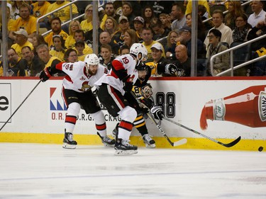 Brian Dumoulin #8 of the Pittsburgh Penguins fights for the puck against Derick Brassard #19 and Zack Smith #15 of the Ottawa Senators during the first period in Game Seven of the Eastern Conference Final during the 2017 NHL Stanley Cup Playoffs at PPG PAINTS Arena on May 25, 2017 in Pittsburgh, Pennsylvania.