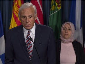 Rania Tfaily, Hassan Diab's wife, looks on as lawyer Donald Bayne responds to a question during a news conference in Ottawa, Wednesday June 21, 2017.