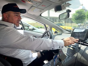 """George Chamoun, chair of the Capital Taxi unit of the taxi union, showed off the new """"smart meter"""" tablet during an event last summer."""