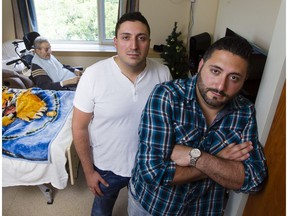 Georges Nassrallah, left, and Daniel Nassrallah, right, are photographed with their grandfather, Georges Karam, background, in his room at the Garry J Armstrong home.
