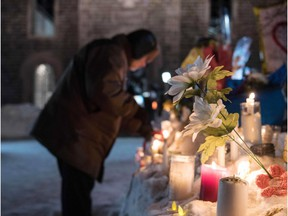 Alexandre Bissonnette was charged Jan. 30 with six counts of murder over a shooting spree at a Quebec mosque -- one of the worst attacks ever to target Muslims in a western country. Above, mourners place flowers at the site of the shooting.