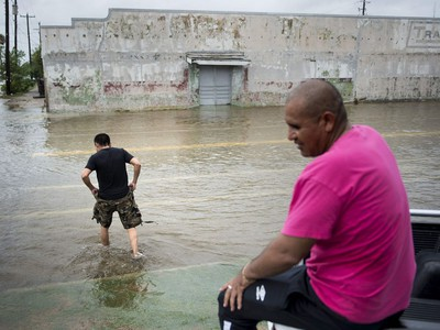 A man wades through water while another sits on a truck as the effects of Hurricane Harvey are seen August 26, 2017 in Galveston, Texas. Hurricane Harvey left a trail of devastation Saturday after the most powerful storm to hit the US mainland in over a decade slammed into Texas, destroying homes, severing power supplies and forcing tens of thousands of residents to flee.