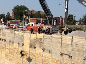 Firefighters lift a victim on a stretcher out of a 75-foot deep construction site on King Edward Friday. The worker suffered a back injury and was in stable condition at the scene.