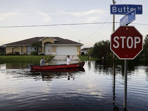 Pierre Ghantos, left, and his son, Nathan, paddle though their flooded neighbourhood in the aftermath of Hurricane Irma in Fort Myers, Fla. on Tuesday.