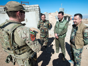 A Canadian special forces soldier, left, speaks with Kurdish Peshmerga fighters at an observation post in northern Iraq.