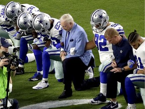 """In this Sept. 25 photo, the Dallas Cowboys, led by owner Jerry Jones, centre, """"take a knee"""" prior to the national anthem before an NFL football game against the Arizona Cardinals."""