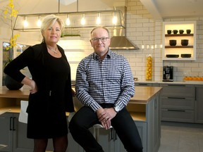Paul St-Germain, who runs a business called Swedish Door that makes doors and accessories to fit with IKEA kitchens, and designer Kim Teron stand inside one of the kitchens they put together during a renovation at a home on Prince of Wales.