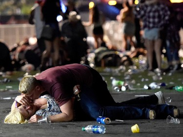 A man lays on top of a woman as others flee the Route 91 Harvest country music festival grounds after a active shooter was reported on October 1, 2017 in Las Vegas, Nevada. A gunman has opened fire on a music festival in Las Vegas, leaving at least 2 people dead. Police have confirmed that one suspect has been shot. The investigation is ongoing.