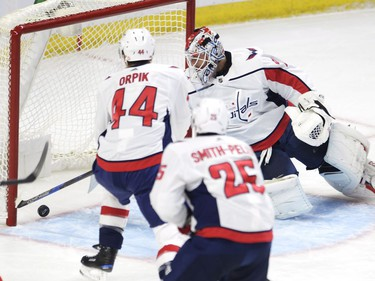 Washington Capitals goalie Braden Holtby (70) pulls the puck our of the net after being scored on by Ottawa Senators defenceman Chris Wideman (not shown) as Brooks Orpik (44) and Devante Smith-Pelly (25) look on during first period NHL hockey action in Ottawa on Thursday, October 5, 2017. THE CANADIAN PRESS/Adrian Wyld ORG XMIT: JFJ501 Adrian Wyld,