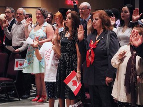 A group of new Canadians takes the citizenship oath at Pier 21 immigration centre in Halifax on Saturday, July 1, 2017. How many newcomers should Canada admit?