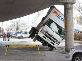 A rental truck being used by Canada Post managed to get stuck under a parking lot ramp at the St Laurent Shopping Centre.  The driver was following a detour around some road construction in the parking area adjacent to St Laurent Blvd and found himself driving under the ramp that didn't have enough clearance.
