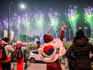 People with a South Korean flag waves as fireworks get off outside the stadium during the opening ceremony of the Pyeongchang 2018 Winter Olympic Games at the Pyeongchang Stadium on February 9, 2018.