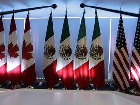 National flags representing Canada, Mexico, and the U.S. are lit by stage lights at the North American Free Trade Agreement, NAFTA, renegotiations, in Mexico City, Tuesday, Sept. 5, 2017. International Trade Minister Francois-Philippe Champagne is briefing senators on Canada's participation in the new Trans-Pacific Partnership trade pact.