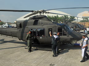 A Philippine Air Force chaplain blesses a newly-delivered Bell 412 helicopter during a christening ceremony in Manila in 2015.