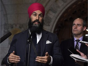 NDP Leader Jagmeet Singh answers a question during an availability following a meeting of the NDP caucus, as MP Guy Caron looks on, on Parliament Hill in Ottawa on Wednesday, Feb. 7, 2018.