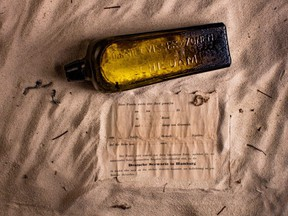 This undated photo received courtesy from Kym Illman on March 7, 2018 shows a bottle and the almost 132-year-old message it contained, that was found near Wedge Island.