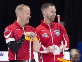 Team Canada skip Brad Gushue, right, and third Mark Nichols react as they watch Newfoundland and Labrador skip Greg Smith playing on another sheet at the Tim Hortons Brier curling championship at the Brandt Centre in Regina on Sunday, March 4, 2018.