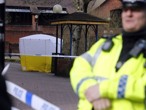"""Police officer secures the area as a police tent covers the the spot in Salisbury, England, Tuesday, March 6, 2018, where former Russian spy double agent Sergei Skripal and his companion were found critically ill Sunday following exposure to an """"unknown substance"""". 66-year old Skripal, and unidentified woman companion are being treated in hospital, after they were found unconscious on the park bench."""