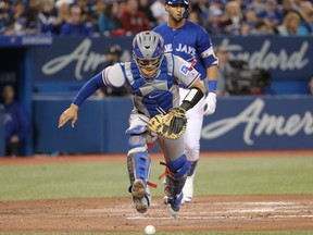 Robinson Chirinos #61 of the Texas Rangers chases the ball that got away on a wild pitch in the fourth inning during MLB game action against the Toronto Blue Jays at Rogers Centre on April 29, 2018 in Toronto.