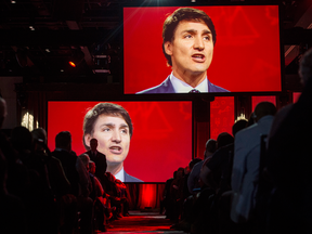 Video screens show Prime Minister Justin Trudeau as he delivers a speech at the federal Liberal national convention in Halifax on April 21, 2018.