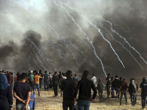 Israeli troops fire teargas at Palestinians during a protest at the Gaza Strip's border with Israel, Friday, April 13, 2018.
