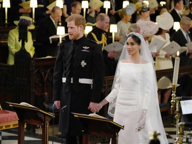 Britain's Prince Harry, Duke of Sussex (L) and US fiancee of Britain's Prince Harry Meghan Markle stand together hand in hand at the High Altar during their wedding ceremony in St George's Chapel, Windsor Castle, in Windsor, on May 19, 2018.