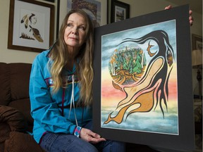 Artist Janet Kaponicin poses with print of her painting the Tragic History behind the Parliament Building.