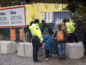 A family, claiming to be from Colombia, is arrested by RCMP officers as they cross the border into Canada from the United States as asylum seekers on April 18, 2018 near Champlain, NY.