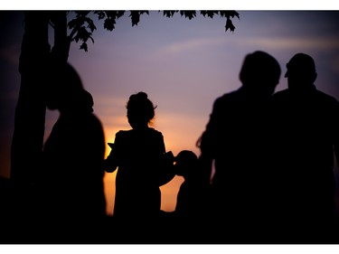 Concertgoers on the hill by the Spin Stage as the sun sets over the Ottawa River.