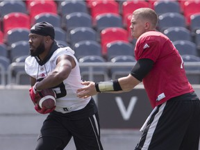 Ottawa Redblacks QB Trevor Harris hands off to RB William Powell during team practice at TD Place on Monday July 16, 2018.