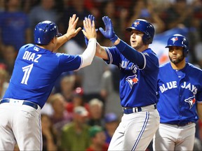 Toronto Blue Jays Justin Smoak high fives Aledmys Diaz hitting a two-run home run in the ninth inning of a game against the Boston Red Sox at Fenway Park on July 13, 2018 in Boston. (Adam Glanzman/Getty Images)