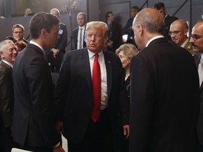 President Donald Trump, center, stops to talk with Spanish Prime Minister Pedro Sanchez, left, and Turkey's President Recep Tayyip Erdogan, right, as they attend a meeting of the North Atlantic Council during a summit of heads of state and government at NATO headquarters in Brussels on Wednesday, July 11, 2018. NATO leaders gather in Brussels for a two-day summit to discuss Russia, Iraq and their mission in Afghanistan.