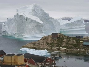 A huge iceberg, near the village of Innarsuit, on the northwestern Greenlandic coast has residents in houses near the shore prepared for an evacuation.