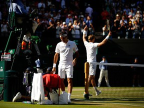 Roger Federer walks to his chair after losing to Kevin Anderson at Wimbledon on July 11.